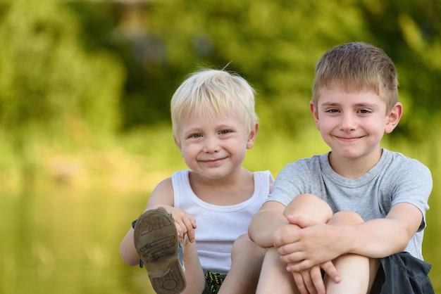 Dwóch małych chłopców siedzi na zewnątrz