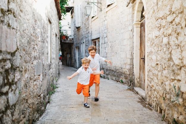 Dwóch małych chłopców w pomarańczowych spodenkach i białych koszulkach biegnie ulicami perast czarnogóry