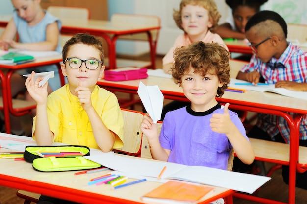 Dwóch małych chłopców w wieku przedszkolnym siedzi przy biurku lub szkolnym stole w klasie, trzymając papierowe samoloty i uśmiecha się