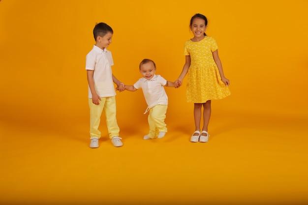 Dwóch małych chłopców w żółtych spodniach i białej koszulce trzyma rękę siostry w żółtej sukience