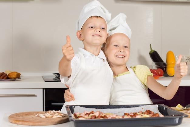 Dwóch małych kucharzy pokazując kciuk do góry, podkreślając dobrą robotę w pieczeniu pizzy.