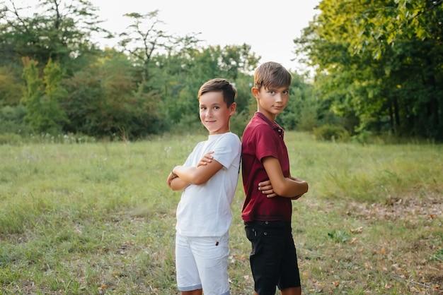 Dwóch małych wesołych chłopców stoi w parku i uśmiecha się