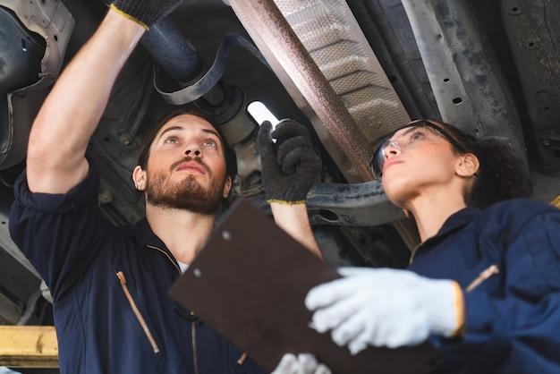 Dwóch mechaników, mężczyzna i kobieta, sprawdzanie i naprawa samochodu w warsztacie samochodowym