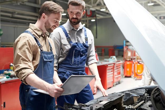 Dwóch mechaników naprawiających samochód