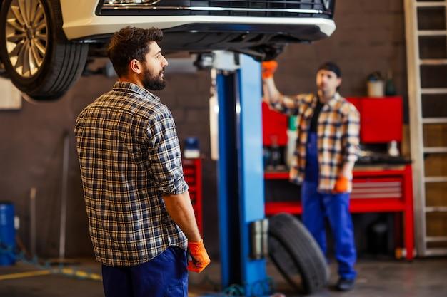Dwóch mechaników pracujących razem nad podniesionym samochodem w warsztacie