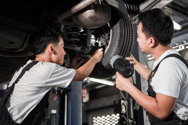 Dwóch mechaników sprawdzało zawieszenie samochodu.