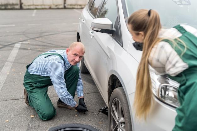 Dwóch mechaników zmieniających koło w samochodzie na poboczu