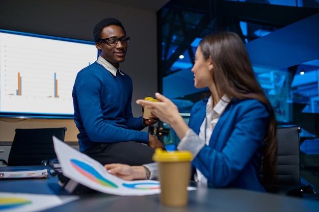 Dwóch menedżerów rozmawia przy stole w nocnym biurze. pracowników płci męskiej i żeńskiej, ciemne wnętrze centrum biznesowego, nowoczesne miejsce pracy