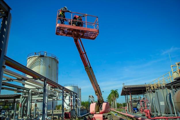 Dwóch męskich gałęzi przemysłu pracujących na wysokości w wysięgniku podnoszącym kontrolę oleju z rurociągów