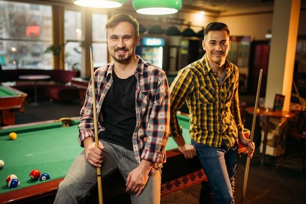 Dwóch męskich graczy w bilard z kijami pozuje przy stole z kolorowymi kulkami