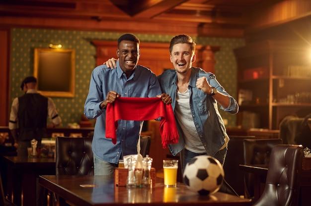 Dwóch męskich kibiców z czerwonym szalikiem i piłką oglądających transmisję w telewizji, przyjaciele w barze