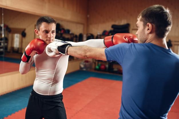 Dwóch męskich kickboxerów w rękawiczkach ćwiczących na treningu w siłowni. zawodnicy na treningu, praktyka kickboxingu w akcji, sparingpartnerzy