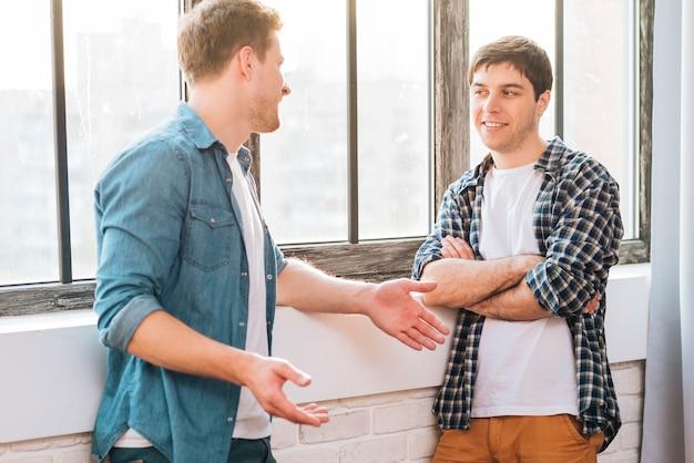 Dwóch męskich przyjaciół stojących przy oknie rozmawiających ze sobą