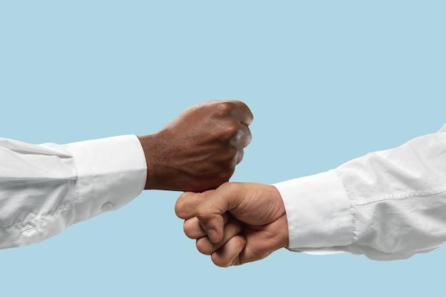 Dwóch męskich rąk konkurencji w siłowaniu się na rękę na niebieskim tle.