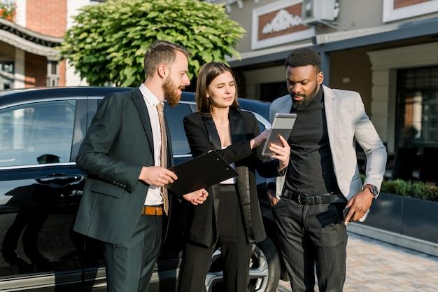 Dwóch mężczyzn, afrykanin i kaukaska, i jedna kaukaska kobieta stoją przed czarnym samochodem na parkingu na dziedzińcu dealera. kobieta pokazuje coś na cyfrowej pastylce