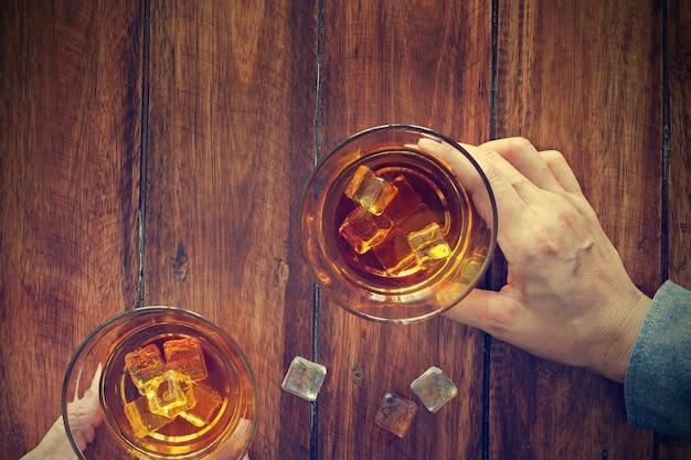 Dwóch mężczyzn brzęczy szklanki whisky razem pijąc napój alkoholowy, podczas gdy w barze w barze.