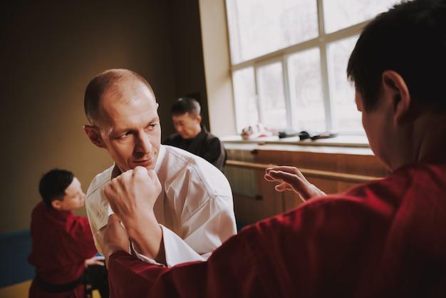 Dwóch mężczyzn ćwiczy technikę uderzenia kung fu na siłowni.
