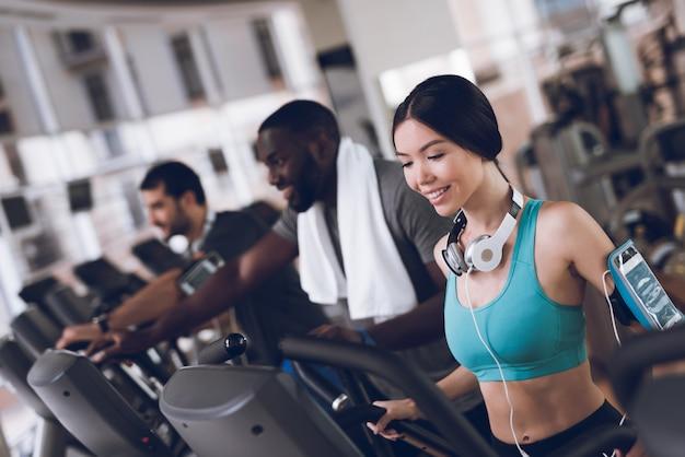 Dwóch mężczyzn i kobieta uśmiechając się ćwiczyć na bieżniach.