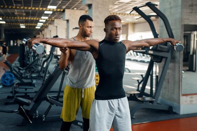 Dwóch mężczyzn lekkoatletycznego robi ćwiczenia z hantlami na treningu w siłowni.