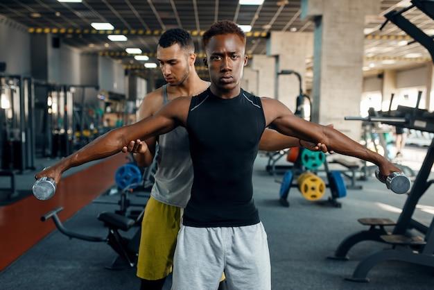 Dwóch mężczyzn lekkoatletycznego robi ćwiczenia z hantlami