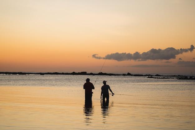Dwóch mężczyzn łowiących ryby w oceanie z plaży o zachodzie słońca