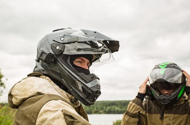 Dwóch mężczyzn na zewnątrz w kaskach i mundurach motocyklowych.