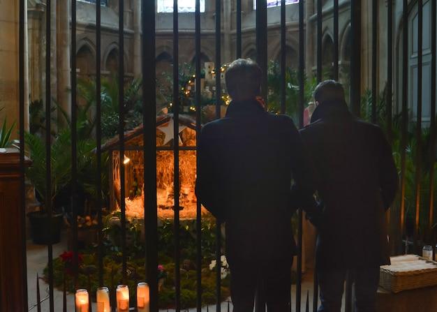 Dwóch mężczyzn patrzących na szopkę bożonarodzeniową z józefem marią i jezusem w kościele z ogrodzeniem ochronnym