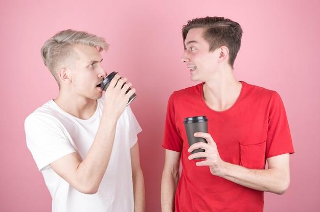 Dwóch mężczyzn pije kawę i uśmiecha się do siebie na różowo