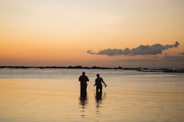 Dwóch mężczyzn połowów w oceanie z plaży o zachodzie słońca