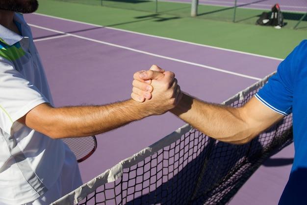 Dwóch mężczyzn, profesjonalnych tenisistów uścisnąć dłoń przed i po meczu tenisowym