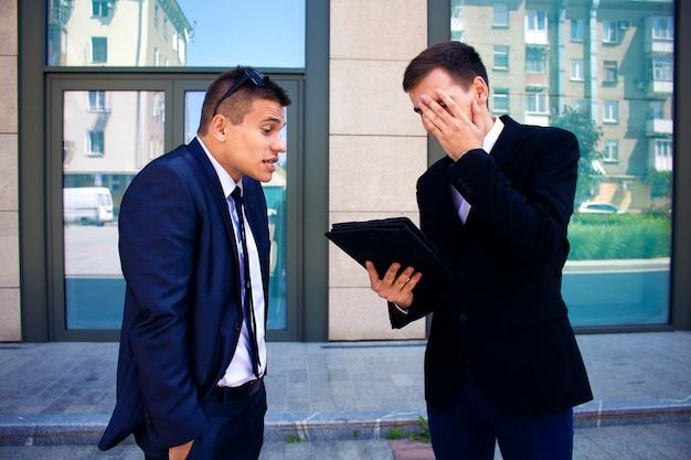 Dwóch mężczyzn prowadzi dialog w pobliżu centrum biznesowego