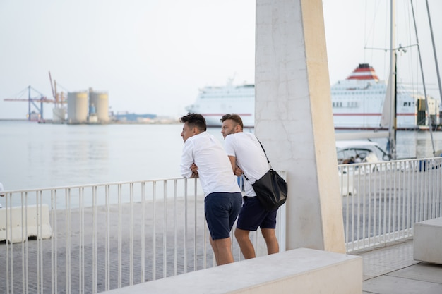 Dwóch mężczyzn przyjaciela na miejskiej promenadzie w maladze
