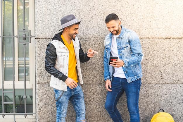 Dwóch mężczyzn przyjaciół przy użyciu telefonu komórkowego na zewnątrz, podczas gdy uśmiecha się.