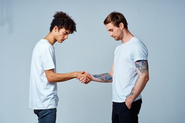 Dwóch mężczyzn przyjaźń ściskając ręce na białym tle