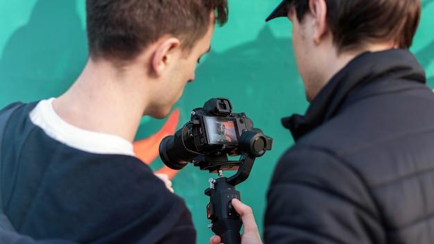 Dwóch mężczyzn rasy kaukaskiej patrząc w ekran aparatu na steadicam, kolorowe tło