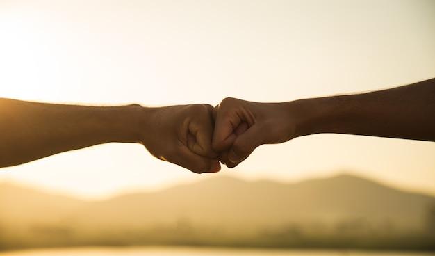 Dwóch mężczyzn ręka daje uderzenie pięścią przed górą podczas zachodu słońca szczęście sukces przyjaźń i koncepcje społeczności