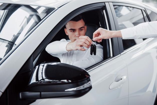 Dwóch mężczyzn stoi w salonie przed samochodami. zbliżenie na kierownika sprzedaży w garniturze, który sprzedaje samochód klientowi. sprzedawca przekazuje klucz klientowi.