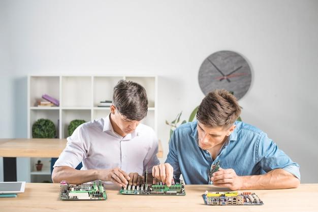 Dwóch mężczyzn technika włożeniu modułu pamięci ram na płycie głównej