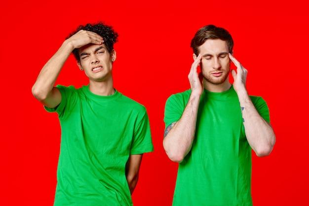 Dwóch mężczyzn trzymających głowy w zielonych koszulkach na czerwonym tle