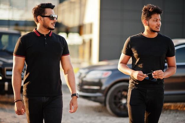 Dwóch mężczyzn ubranych na czarno, pozujących w pobliżu suvów