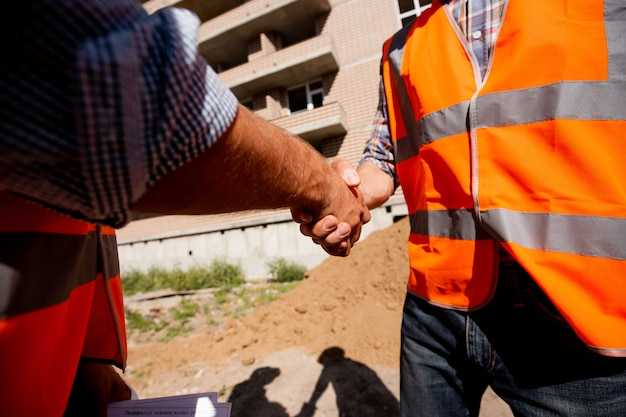 Dwóch mężczyzn ubranych w koszule i pomarańczowe kamizelki robocze ściskają sobie ręce na tle wielopiętrowego budynku.