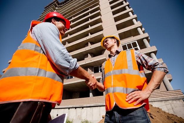 Dwóch mężczyzn ubranych w koszule, pomarańczowe kamizelki robocze i hełmy podają sobie ręce na tle wielopiętrowego budynku.