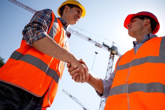 Dwóch mężczyzn ubranych w pomarańczowe kamizelki robocze i hełmy ściskają sobie ręce na placu budowy w pobliżu dźwigu. .