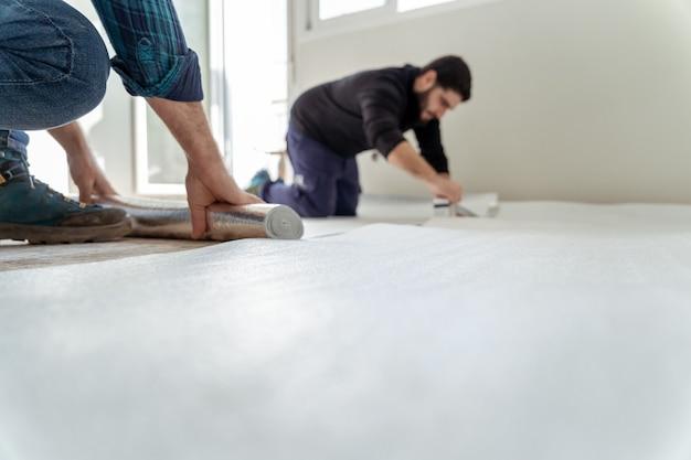 Dwóch mężczyzn układających warstwę izolacyjną na podłodze domu