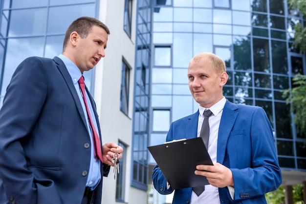 Dwóch mężczyzn w garniturach ze schowkiem i kluczami negocjuje