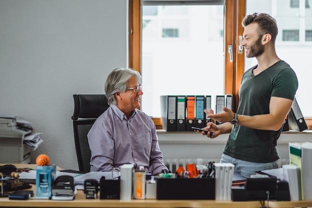 Dwóch mężczyzn w różnym wieku w biurze, partnerzy biznesowi