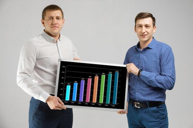Dwóch mężczyzn w ubraniach biznesowych, trzymając deskę ze statystykami na białym tle