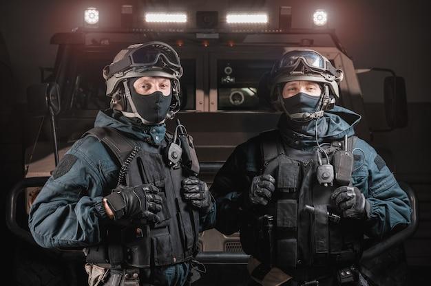 Dwóch mężczyzn w wojskowych mundurach stoi w hangarze z ciężarówką