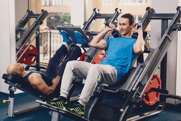 Dwóch mężczyzn wykonuje ćwiczenia fizyczne na siłę nóg