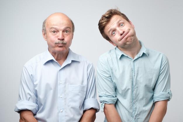 Dwóch mężczyzn wykrzywiających się, nadymających policzki, wstrzymujących oddech